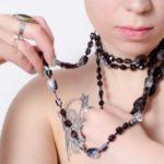 黒いネックレスを巻く女性とタトゥー