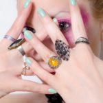 指輪をはめた手で顔を隠す女性